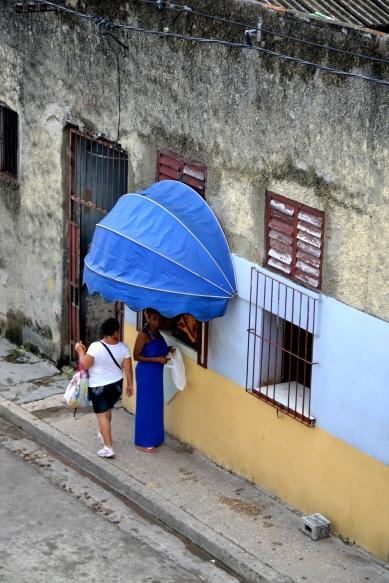 De overbuurvrouw verkoopt vlees vanaf haar vensterbank.